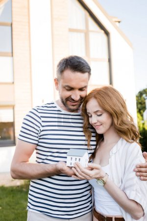 Photo for Smiling couple hugging and looking at statuette of house on blurred background - Royalty Free Image