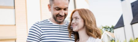 Photo for Smiling redhead woman looking at man with blurred house on background, banner - Royalty Free Image