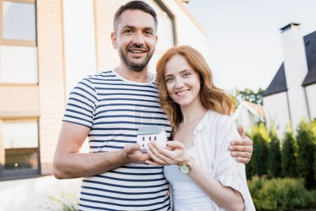 Photo for Smiling couple with statuette of house looking at camera and hugging on blurred background - Royalty Free Image