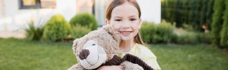 Portrait of smiling girl with teddy bear looking at camera on blurred background, banner
