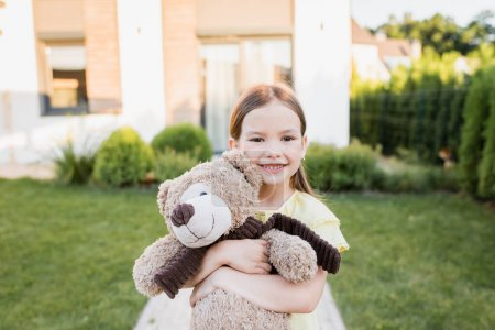 Photo for Happy girl with teddy bear looking at camera with blurred house on background - Royalty Free Image
