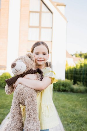 Smiling girl looking at camera while hugging teddy bear with blurred home on background