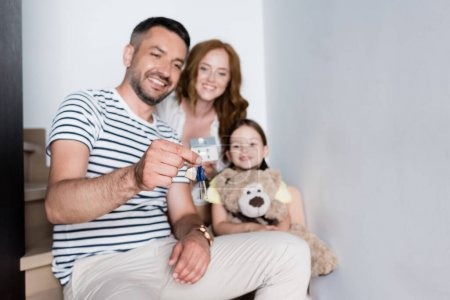 Photo for Smiling girl and woman looking at keys in hands of man while sitting on stairs at home on blurred background - Royalty Free Image