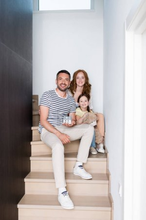 Photo for Happy family with teddy bear and statuette of house looking at camera while sitting on stairs at home - Royalty Free Image