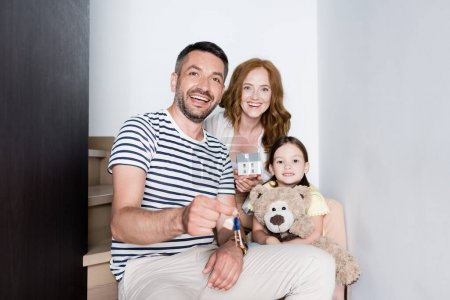 Photo for Happy man showing keys while sitting on stairs near woman with statuette of house and girl with teddy bear at home - Royalty Free Image