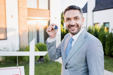 Photo for Happy broker showing keys while looking at camera on blurred background - Royalty Free Image