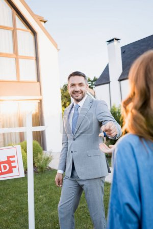 Smiling broker looking at camera while giving keys to blurred woman on foreground