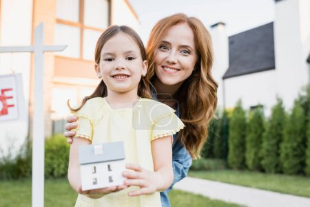Photo for Redhead mother hugging daughter with house statuette while looking at camera with blurred houses on background - Royalty Free Image