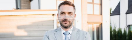 Photo for Confident bearded broker looking at camera with blurred houses on background, banner - Royalty Free Image