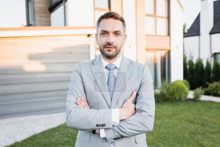 Photo for Confident broker with crossed arms looking at camera with blurred houses on background - Royalty Free Image