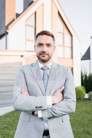 Photo for Front view of confident broker with crossed arms looking at camera with blurred house on background - Royalty Free Image