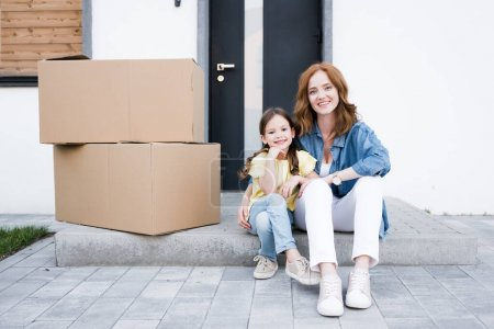 Photo for Smiling redhead mother hugging daughter while sitting on doorstep near carton boxes - Royalty Free Image
