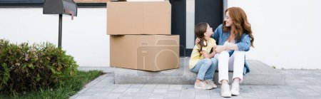 Photo for Cheerful mother and daughter looking at each other while sitting near carton boxes on doorstep, banner - Royalty Free Image