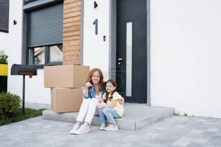 Photo for Happy redhead woman looking at key and hugging daughter while sitting on doorstep near cardboard boxes - Royalty Free Image