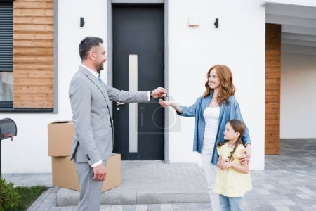 Photo for Happy broker giving key for woman with daughter near carton boxes on doorstep - Royalty Free Image