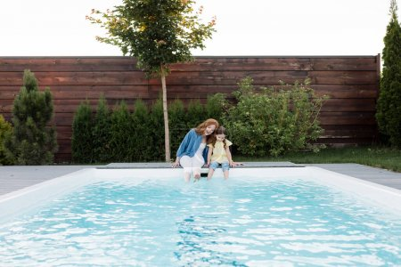 Photo for Happy mother and daughter sitting with legs in swimming pool on backyard - Royalty Free Image