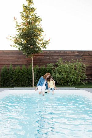 Photo for Cheerful mother and daughter sitting with legs in swimming pool on backyard - Royalty Free Image