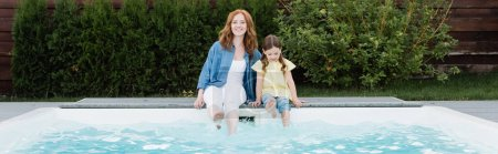 Photo for Cheerful redhead mother looking at camera while sitting with daughter near swimming pool on backyard, banner - Royalty Free Image