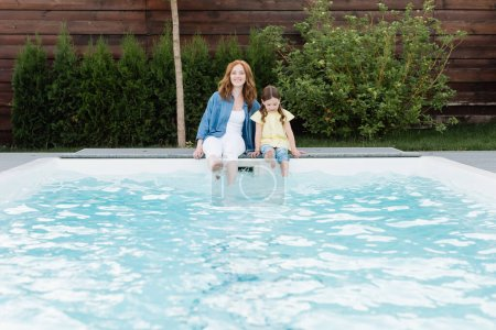 Photo for Smiling mother looking at camera while sitting near daughter near swimming pool on backyard - Royalty Free Image