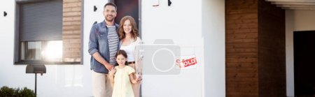 Happy family looking at camera while standing together near house and sign with sold lettering, banner