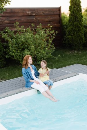 Photo for High angle view of happy mother and daughter sitting with legs in swimming pool near lawn with bushes on backyard - Royalty Free Image