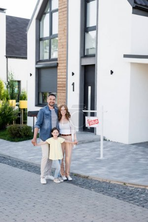 Photo for Happy family hugging and looking at camera while standing near house and sign with sold lettering - Royalty Free Image