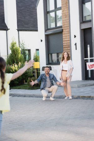 Redhead woman standing near man squatting with open arms while looking at daughter on blurred foreground