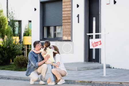 Photo for Happy parents squatting and hugging daughter near house on blurred background - Royalty Free Image
