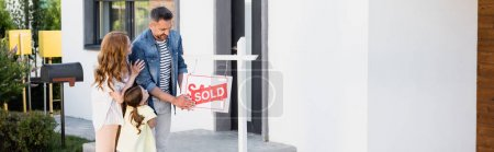 Photo for Positive father holding sign with sold lettering near wife and daughter, banner - Royalty Free Image