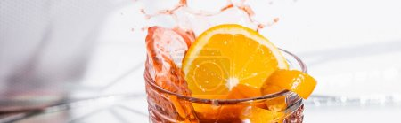 écorce d'orange en verre avec cocktail d'alcool éclaboussé sur blanc, bannière