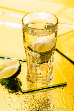 Photo for Sliced lime in glass with alcohol cocktail on yellow - Royalty Free Image
