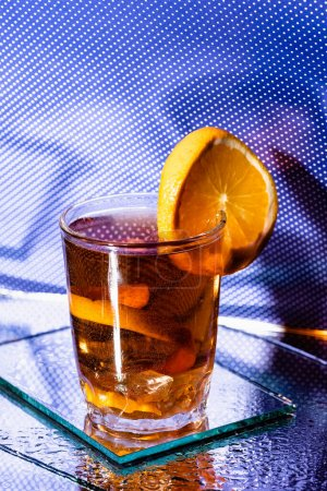 glass with mixed cocktail and sliced orange of blue