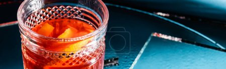 Photo for Mixed alcohol cocktail with whiskey and orange on blue, banner - Royalty Free Image
