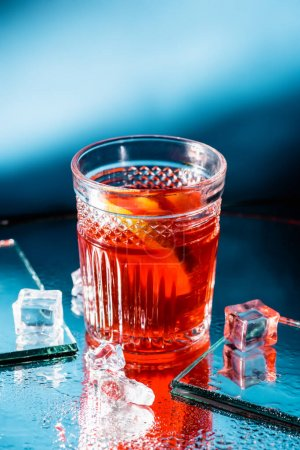 Photo for Mixed alcohol cocktail with whiskey near ice cubes on blue - Royalty Free Image