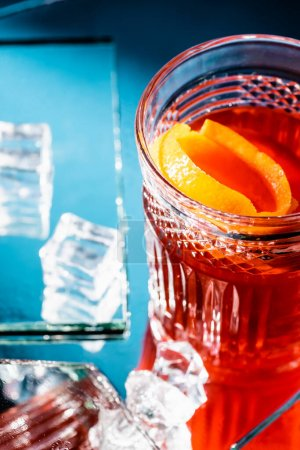 mixed alcohol cocktail with whiskey and orange near ice cubes on blue