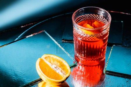 cóctel de alcohol mezclado cerca de la mitad de naranja en azul