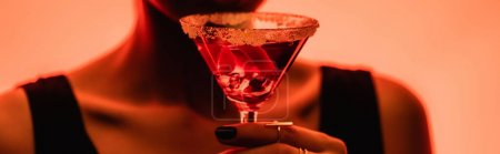 Photo for Margarita cocktail with ice cubes and salt in hand of woman on blurred orange background, banner - Royalty Free Image