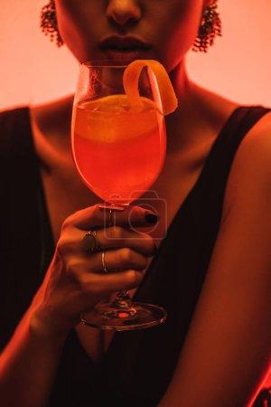 vista parcial de elegante mujer sosteniendo vidrio con cóctel mixto y naranja en rosa