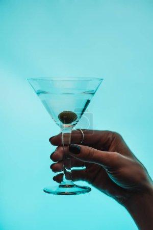 abgeschnittene Ansicht einer Frau mit einem Glas Martini mit Oliven isoliert auf Blau
