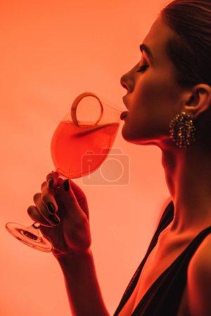 Photo pour Profil de la femme tenant verre avec cocktail mixte et écorce d'orange sur rose - image libre de droit