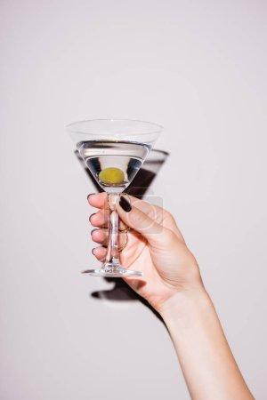 abgeschnittene Ansicht einer Frau mit einem Glas Martini mit Oliven auf Weiß