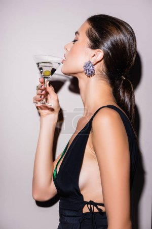 Photo for Side view of woman drinking martini with olive on white - Royalty Free Image