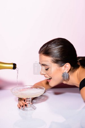 cheerful woman looking at champagne in glass near bottle on white