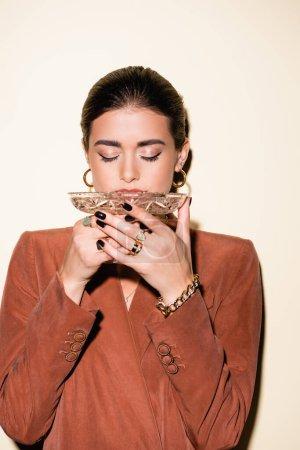 Photo pour Femme brune en blazer marron buvant du champagne sur verre blanc - image libre de droit