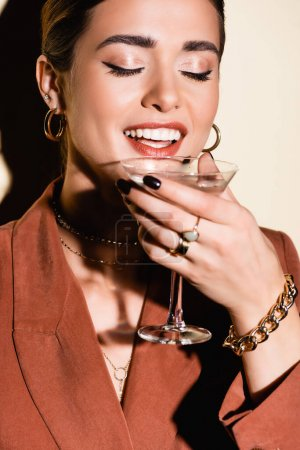 Photo for Happy woman holding glass of alcohol drink on white - Royalty Free Image