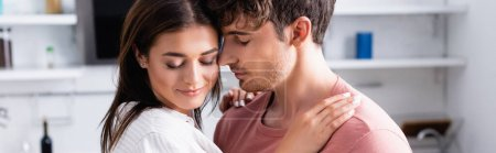 Young woman embracing shoulders of boyfriend with closed eyes on kitchen, banner