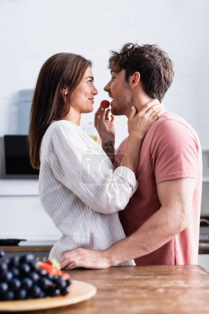 Photo for Side view of smiling woman hugging and feeding boyfriend with strawberry near grape on blurred foreground - Royalty Free Image