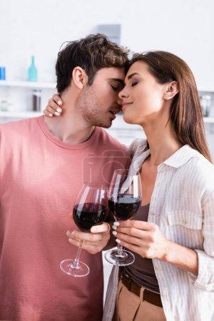 Photo pour Jeune femme tenant un verre de vin et câlin petit ami avec les yeux fermés dans la cuisine - image libre de droit