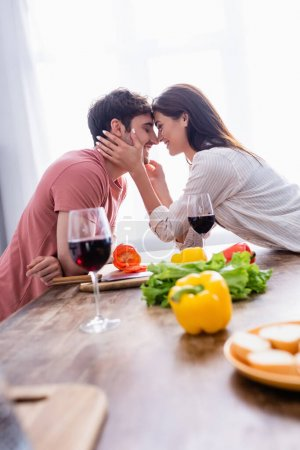 Smiling woman touching face of boyfriend near wine and vegetables on blurred foreground