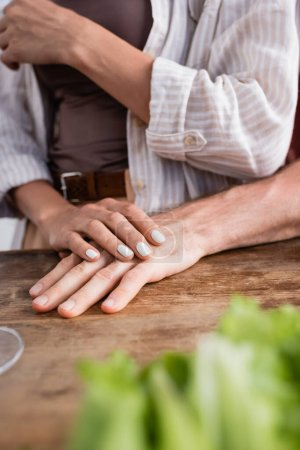 Cropped view of woman holding boyfriend hand on kitchen table on blurred foreground